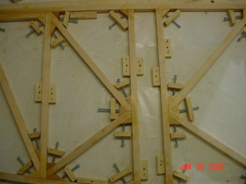 Blocks with screws to apply pressure to gussets epoxied in corners