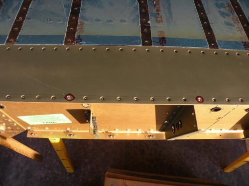 Countersunk holes for rivets that will attach the aft ends of the forward floor stiffeners.