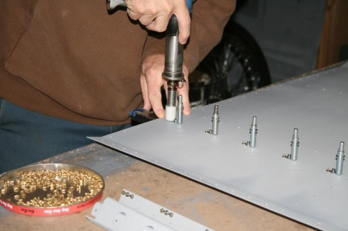 Backriveting the nutplates onto the fwd floor panel.
