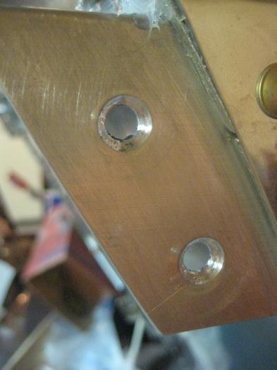 Countersunk holes in engine mount brackets.