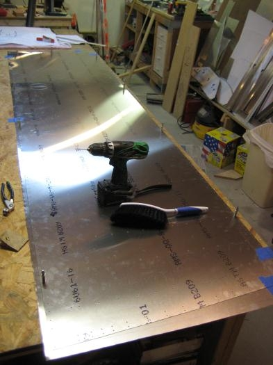 Completed skin to act as pattern, on top of rough cut aluminum sheet for second skin. Note clecos.