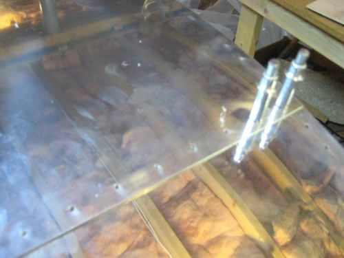 Leading edge UNDER the aft top skin, for locating holes in leading edge skin (rafters in reflection).
