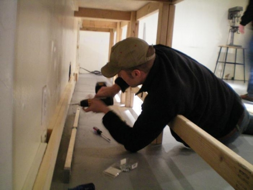 Chris screwing 1x4 to the wall under the bench