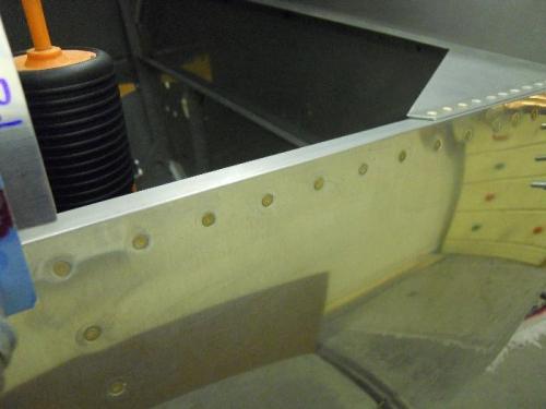Side skin riveted in baggage door opening